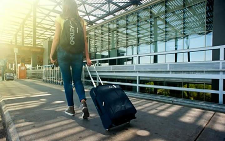 Mulher puxando mala de viagem - Grávida pode viajar de ônibus