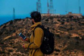 Pessoa com celular na mão e mochila