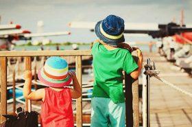 Crianças de costas com mala de viagem